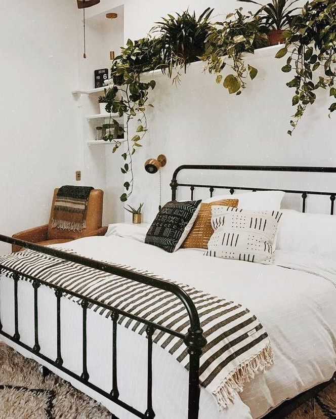 White walls and white linen bedroom come to life with tribal pillows and live indoor plants