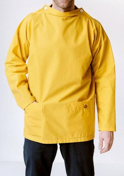 Waxed Yellow Woodturner's Smock.  Based on the traditional fisherman's smock our version is a slightly tighter cut and incorporates the double button hole design on either shoulder with white overall buttons to pinch in the collar snug around the neck to stop the wood shavings (and rain) blowing down the front.   Made to order in a numbered edition, the Woodturner's Smock is a functional and hardwearing top layer, in 250gsm 100% waxed cotton canvas.