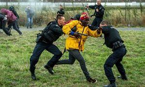 Gendarmi francesi cercano di fermare i migranti sul sito Eurotunnel a Coquelles vicino a Calais.