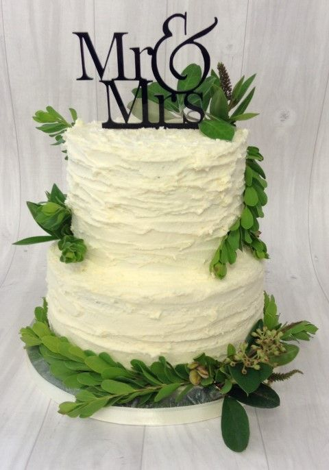 Outdoors style wedding cake. Simple frosted 2 tier cake, complete with greenery and a custom Mr & Mrs Topper in black acrylic.