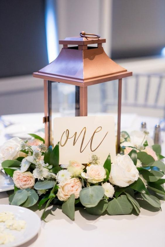 copper lantern and greenery eucalyptus wedding centerpiece