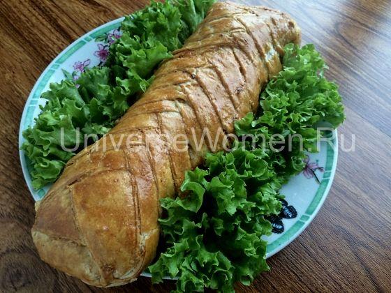Охлаждаем, нарезаем, выкладываем мясной рулет в тесте красиво на блюдо, украшаем зеленью или листьями салата и подаем на стол.