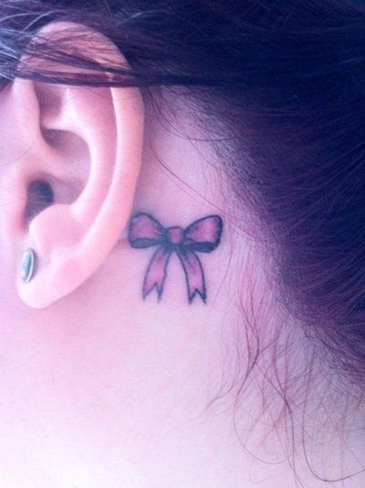 pink bow behind the ear tattoo