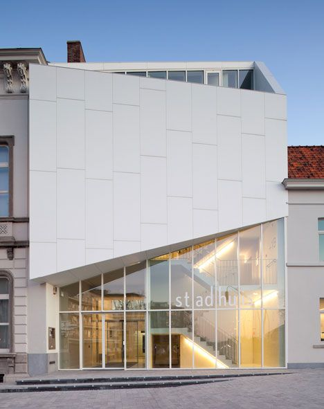 City Hall office in Belgium by Dehullu Architects / The white panels that clad the facade are made from Corian and they skew upwards to partially screen a balcony on the second floor.