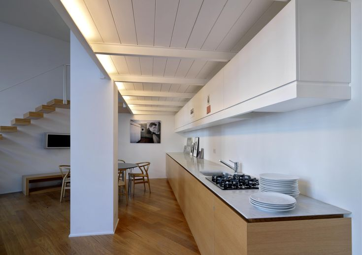 Loft - via Maiocchi - Milano Fabio Azzolina architect - Loft - via Maiocchi - Milano The living room is characterized by the long kitchen mono block. The office area is reached from the living room by a cantilever stairway.