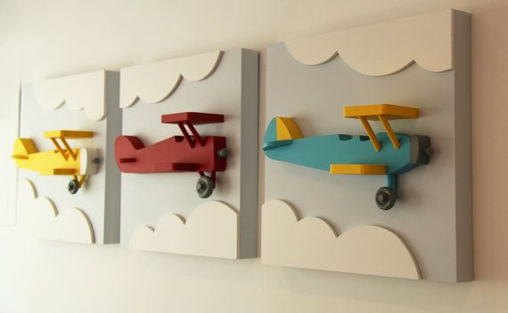 Set of 3 vintage style wood biplanes in dark red, bright yellow, and teal. Each wood airplane extends out from a square base with raised clouds for a 3D effect that will add flair to an airplane themed baby room, nursery, or kids room with an aviation or transportation theme. Handcrafted from birch, pine and MDF, this wood wall art makes a great alternative to canvas art and prints. DIMENSIONS OF EACH PIECE: Square Base Height: 14 inches tall Square Base Width: 14 inches wide Base Thickn...