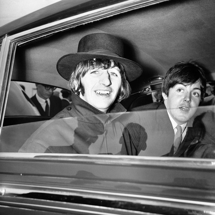 Ringo Starr grins cheerfully at fans as he drives, with Paul McCartney, from London airport on July 4, 1965, after the tousle-haired pop group returned from a European tour that played to less than capacity houses and received a relatively subdued welcome from about 1,000 young screamers, mostly girls. (AP Photo)