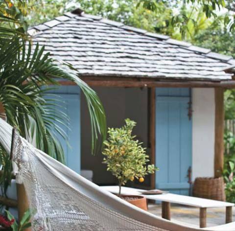 """Casa em Trancoso, BA, erguida com eucalipto e coberta com telhas de madeira: O casamento da parede branca com a porta azul não é fruto do acaso e se repete pela construção. """"Queríamos homenagear Iemanjá, a Rainha do Mar"""", conta a proprietária."""
