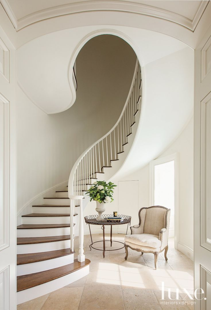 A sinuous spiral staircase graces the entry. The antique chair upholstered in vintage linen is from The Gray Door, while the antique iron table beside it was purchased at M. Naeve.