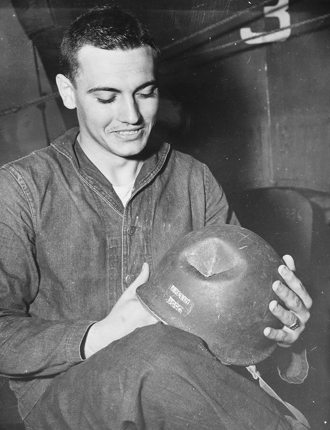 O marinheiro americano da foto teve sua cabeça atingida por de arma nazista .30, rasgando seu capacete com uma perfuração de 2 polegadas, teve sorte, embora muitos outros marinheiros que tiveram suas embarcações de transporte de pessoal e material não tiveram.