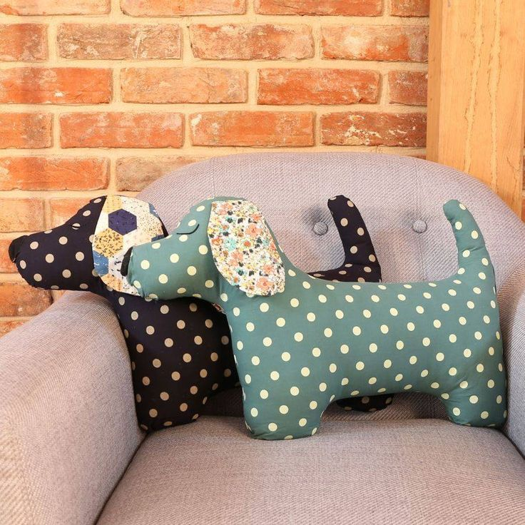A polka dot patterned sausage dog shaped cushion