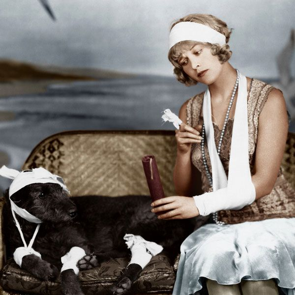 They didn't have the Internet in the early 20th century, so this young woman can't figure out whether to give her dog aspirin. Injured woman and injured dog by Shutterstock.