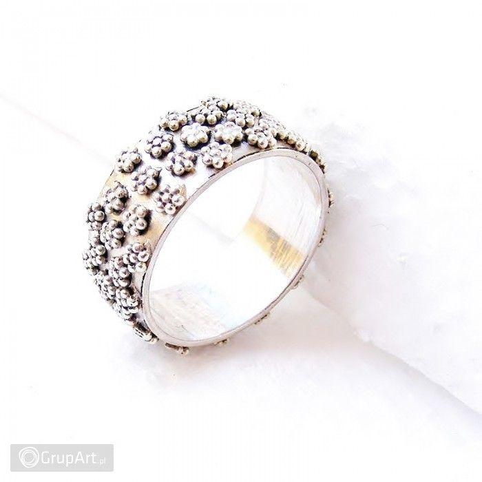 Niewinna, wyrazista obrączka wykonana ze srebra próby 925. Na srebrnej bazie obrączki rosną drobne, srebrne kwiatki :) Lekko wypukłe, co nadaje obrączce nieco przestrzennego charakteru. Piękna, jedyna w swoim rodzaju. Jasne, polerowane srebro. Będzie pięknie wyglądać na lekko opalonej dłoni. Rozmiar jubilerski 17,5 do 18. Szerokość 1 cm. #obraczka #bizuteria #handmade #srebro #grupart Inne obrączki dostępne w Grupart.pl: http://www.grupart.pl/obraczki-191.html