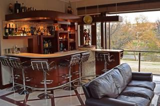 House for sale in Dainfern Valley The indoor/outdoor bar complex has river frontage views and allows lavish entertaining without compromising the privacy of the home.