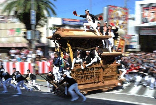 """勇壮な「やり回し」が繰り広げられた「岸和田だんじり祭」で、34台は市街地を疾走する。Yuusou na """"yari mawashi"""" ga kuri hirogerareta """"Kishiwada Danjiri Matsuri"""" de, 34 dai wa shigaichi wo shissou suru. Di """"Festival Danjiri Kishiwada"""" di mana digelar """"belok cepat tikungan"""" yang berani, 34 pedati mengebut di jalanan kota."""