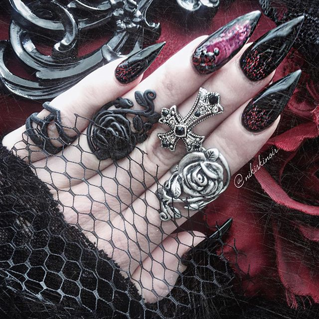 """.  Loving my super sharp set of claws done by @nailsbymiyah ! The nail on my ring finger is actually an aquarium nail with moving """"bloody"""" liquid and glitter!   .  Midi ring worn as pinky ring from @rogueandwolf, all other rings from Japan   .  #nailporn #gothicnails #gothgoth #aquariumnails #nailart #rogueandwolf #gothicjewelry #stilettonails #clawnails #gothicstyle"""