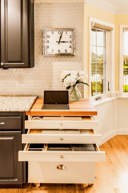 Hidden charging cabinet keeps everything from ending up on the kitchen counter. Transitional  by Design Harmony