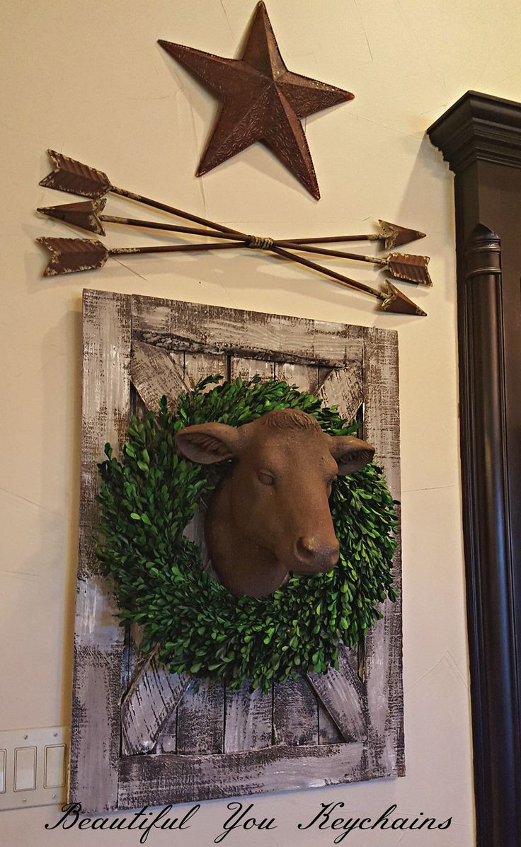 I'm finally getting around to designing the bare walls in our family room.  My cow head is my pride and joy!  She has a boxwood leaf wreath and is mounted on a mini barn door that is made out of genuine barn wood.  Arrows and the symbol of Texas...the star, complete this section of our wall.  Posted on my business page, Beautiful You Keychains on FB.
