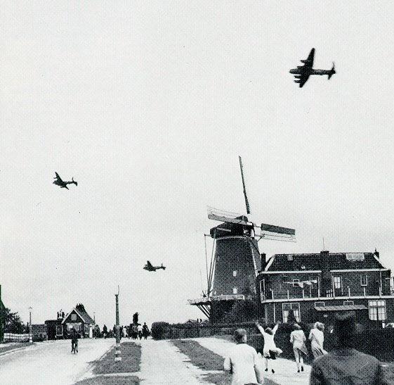 Het afwerpen van voedsel door Lancaster vliegtuigen van de RAF bij de Terbregseweg in Rotterdam. Op de voorgrond: de korenmolen de Vier Winden aan de Terbregse Rechter Rottekade. De fotograaf is H.F. Grimeyer en de foto is gemaakt op 29 april 1945.