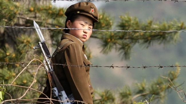 Un soldado norcoreano mujer se asoma desde detrás de una valla de alambre de púas en torno a un campamento en las orillas de los ríos de Corea del Norte.