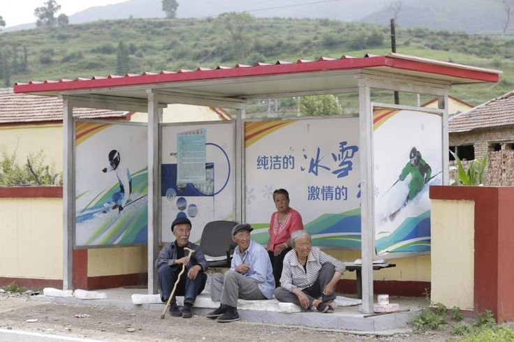 Local villagers rest at a bus station near Wanlong Ski Resort, which could host some Olympic skiing events, in Chongli county of Zhangjiakou, China, which is jointly bidding with the capital Beijing to host the 2022 Winter Olympic Games, July 30, 2015. Beijing, which hosted the 2008 Summer Olympics Games, hopes to beat Almaty, Kazakhstan, and win the 2022 Winter Olympics, when a decision is made on Friday in the Malaysian capital, Kuala Lumpur. REUTERS/Jason Lee