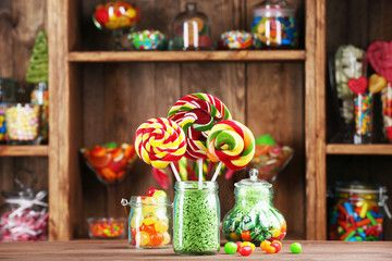 Colorful candies in jars on table in shop