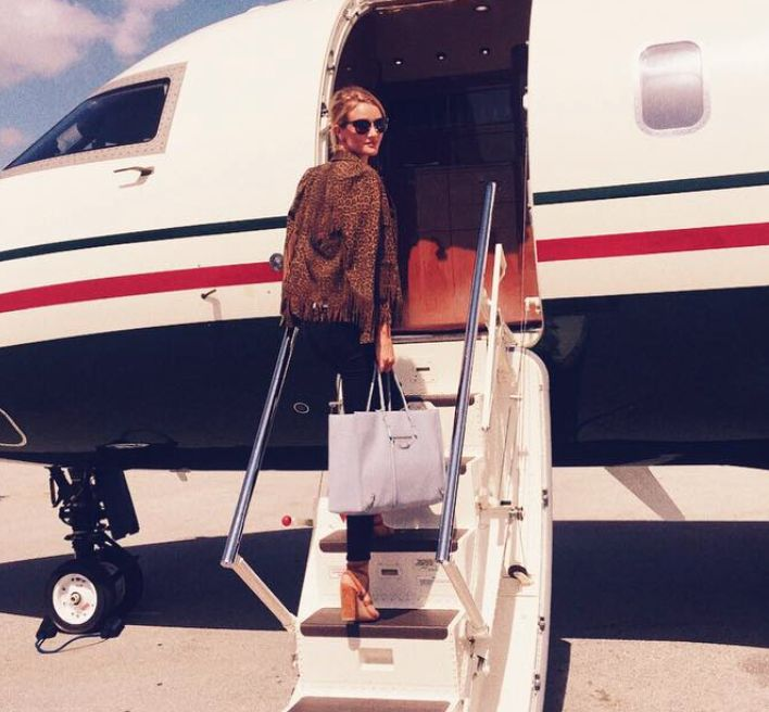 Rosie Huntington Whiteley boards her private jet in a Saint Laurent jacket. CASUAL.
