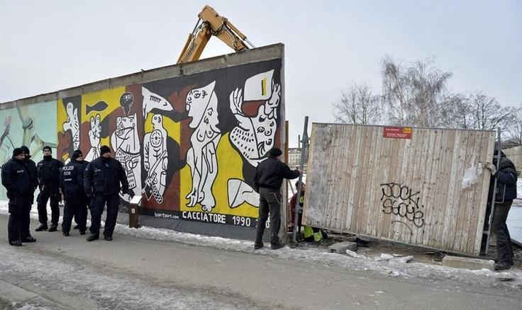 Tem início a polêmica construção de um condomínio de luxo no centro de Berlin, Alemanha. Para sua edificação, parte do muro de Berlin teve de ser removido, causando manifestações pela capital do país - http://revistaepoca.globo.com//Sociedade/fotos/2013/03/fotos-do-dia-27-de-marco-de-2013.html (Foto: EFE/Britta Pedersen)