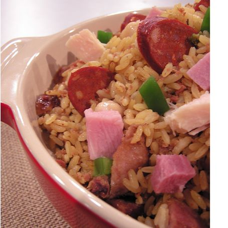 Lazy Rice  4 slices bacon   ¼ cup olive oil   ½ cup chopped onion   ¼ cup green pepper   2 chorizos sliced   ​​1 can 10 oz. shredded chicken   1 can Corned Beef   1 cup cooked ham   1 can chickpeas   4 cups chicken or beef broth   4 cups long grain rice   salt to taste  In a saucepan put all of the above stir, cover & cook over md. heat for 30 to 35 minutes. Tip You can prepare this recipe in the oven: getting all the ingredients in a baking pan and covering with foil. Bake for 50 min