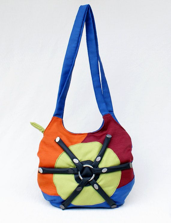 Shoulder bag with double strap, handmade with green, orange, blue and bordeaux furniture fabric, decorated on the front side with recycled bike tubes, metal ring and buttons with chrome effect.