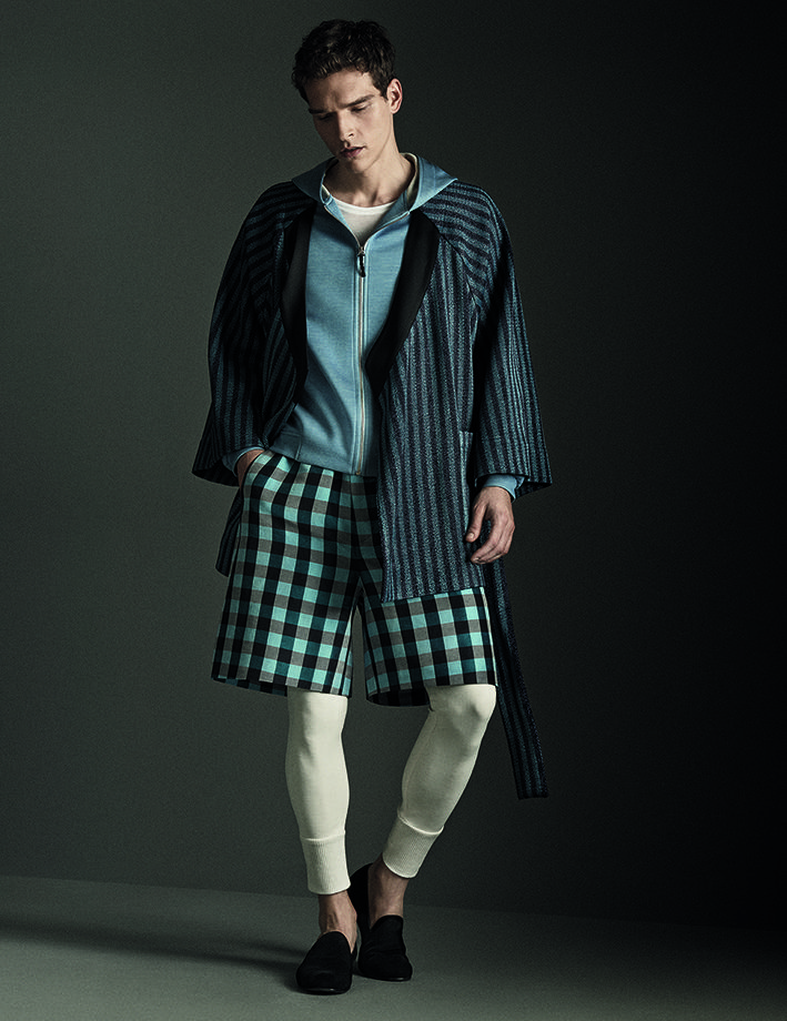 Short striped kimono in raffia worked on a loom, worn over a hooded jersey-silk blue jacket with pearl-white cotton lining. Knee-length shorts in linen and silk featuring large chequered pattern, worn over long johns with a high thin-ribbed hem.