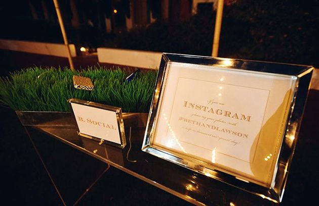 Cell phone charging station in planters of grass at the wedding reception
