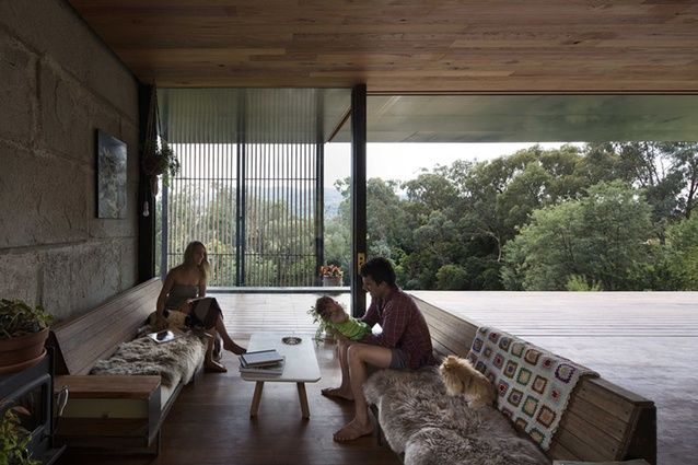 A custom timber screen and stacking doors partition the indoor and outdoor spaces.