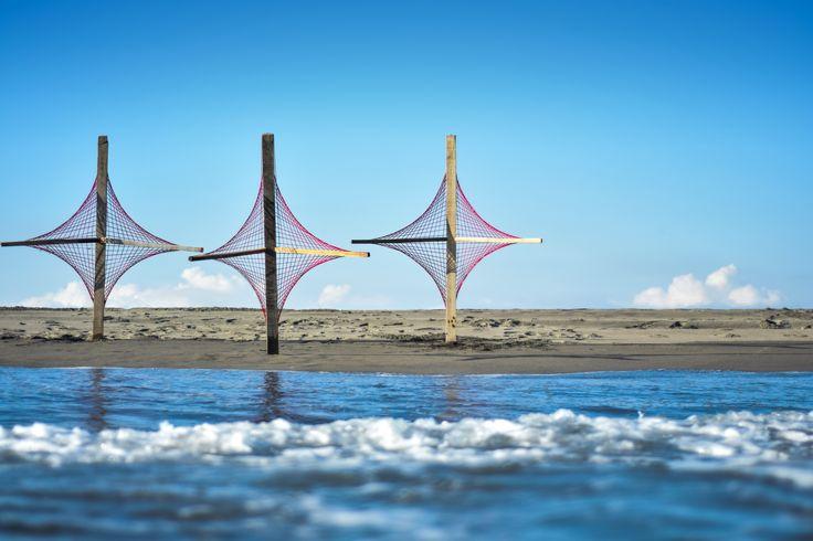 Capturar el aire | TECTÓNICAblog  Intervenir el paisaje y capturar su esencia fue el objetivo principal del objeto creado. El mar su visual y su profundidad se escapan a nuestras manos. La única manera de apropiarnos y tocar el paisaje es por medio del aire. La brisa pasa por medios de hilos de estambre tejido en forma hiperbólica lo cual intensifica los decibelios y lo hace perceptible intensamente.  El evento trata sobre Intervenir el paisaje sin tocarlo ni modificarlo. El objeto fue…