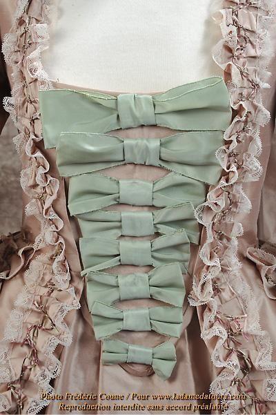 Robe à la française satin rose avec pièce d'estomac orné d'échelle de rubans vert céladon.