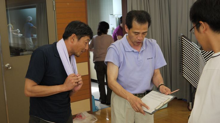"""Our grower-artisan Koji Nagata (left) checking out judges' scores on a new varietal at the Kumamoto Prefecture Tea Research Center (""""Chaken""""), where researchers test teas bred for natural taste and hardiness, for instance."""