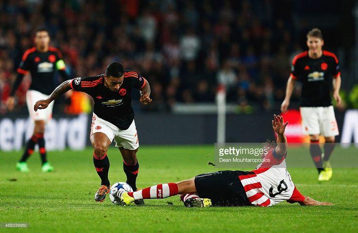 Luuk de Jong of PSV Eindhoven slides to tackle Memphis Depay of Manchester United