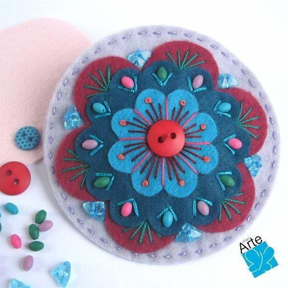 Fivela com aplique em feltro, com bordados e aplicação de botões e contas. Dimensões: 10 cm de diâmetro. Acabamento perfeito, com fivela longa.