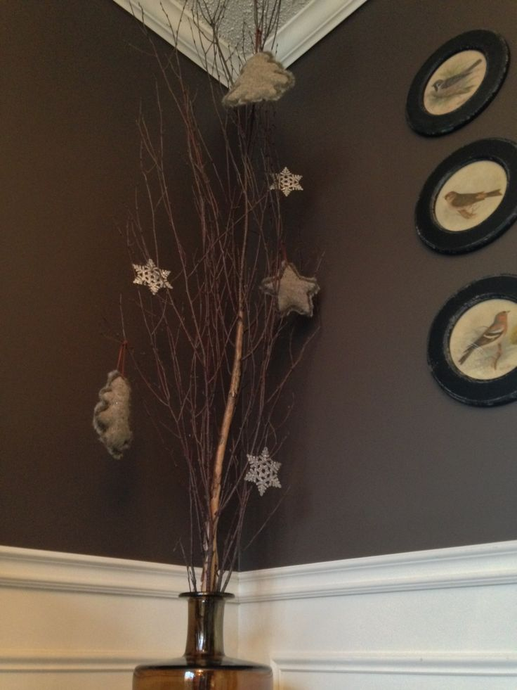 Simple ornaments hang from a birch branch in a tall vase.