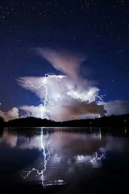 """Wow - clouds seemingly """"out of the blue"""" literally shoot out lightning that reflects on the lake"""