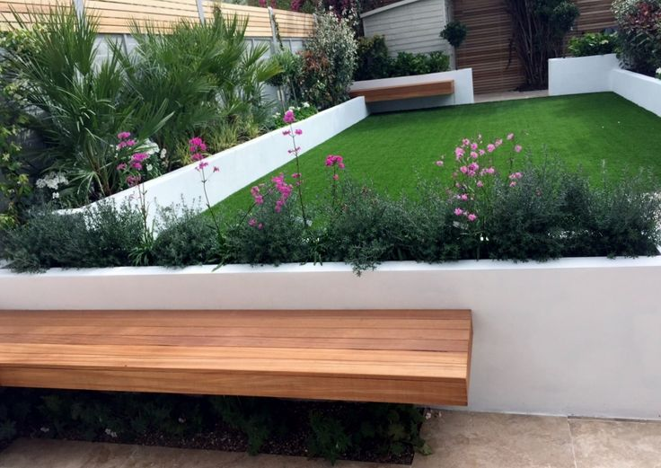 artificial grass raised render painted beds travertine paving grey fence hardwood floating bench