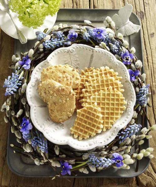 Обрамите тарелку с выпечкой красивым веночком из ветвей вербы и маленьких первоцветов. За основу возьмите проволочное кольцо (купите в магазине для флористов или сделайте сами). Уложите всю эту красоту на поднос, а в центр поставьте белое блюдо с угощением.