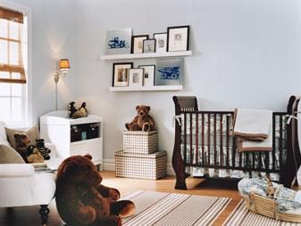 A classic nursery for a baby boy. Baby blue walls paint color, chocolate brown crib, striped brown rug, white chair with caster legs, and white floating shelves. Farrow & Ball Borrowed Light