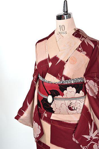 葡萄茶色と象牙色の大胆な段違い縞に可憐な梅の花枝と小粋な笹の葉が浮かび上がる、大正ロマン・昭和レトロな詩情ただよう古典文様が織りだされたアンティークの袷着物です。