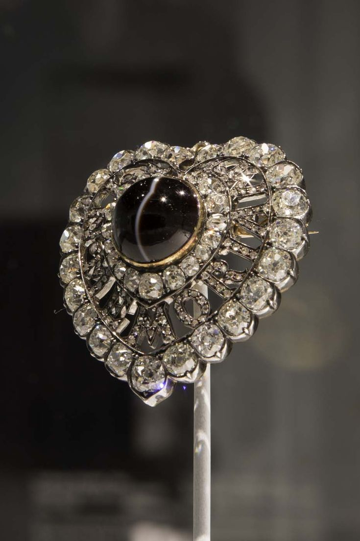 "The prestigious Rothschild collection has lent some outstanding examples of Victorian Mourning jewelry, including a heart-shaped diamond brooch with the words ""In Memoriam"" spelt out in a display of virtuoso craftsmanship."