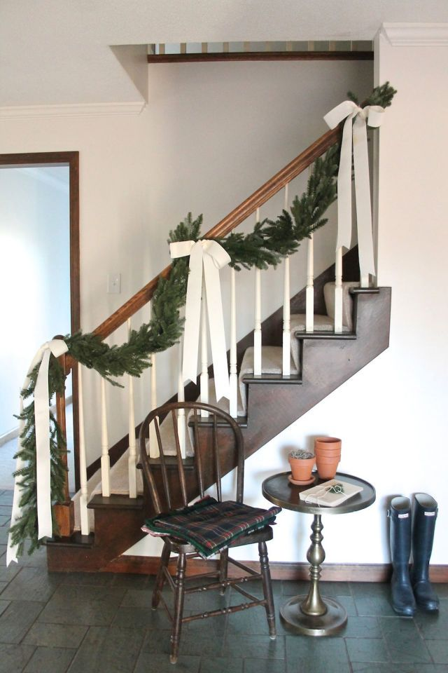 Christmas decorating with garland and pine boughs, although I like the look of the stairwell in general here with white balusters and dark stringers.