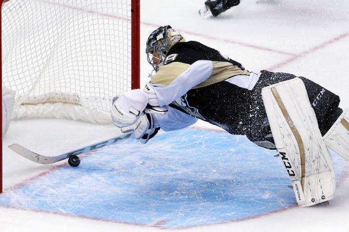 Pittsburgh Penguins goalie Marc-Andre Fleury dives and stops the puck from crossing the goal line on a shot by Columbus Blue Jackets' Cam Atkinson during the third period of an NHL hockey game in Pittsburgh Friday, Nov. 13, 2015. The Blue Jackets won 2-1. (AP Photo/Gene J. Puskar)