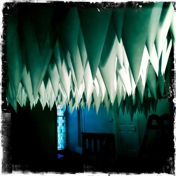 Pop up paper installation in small old church made up of lots of suspended paper cones. Www.kingstonlaffertydesign.com