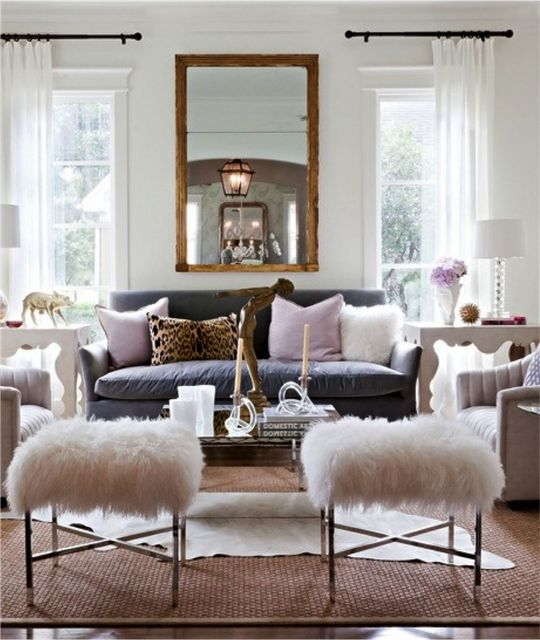 Like the mirror between windows, curtains on one side of the window. Rug with another rug on top. Luv the white fur ottomans...