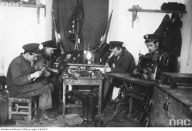 """Pracownia szewska. Z prawej maszyna do szycia marki """"Singer"""". W tle ustawione karabinki Mannlicher M1895 z otwartymi zamkami (1. i 2. z lewej). / Źródło: NAC, sygn. 1-B-61-2"""